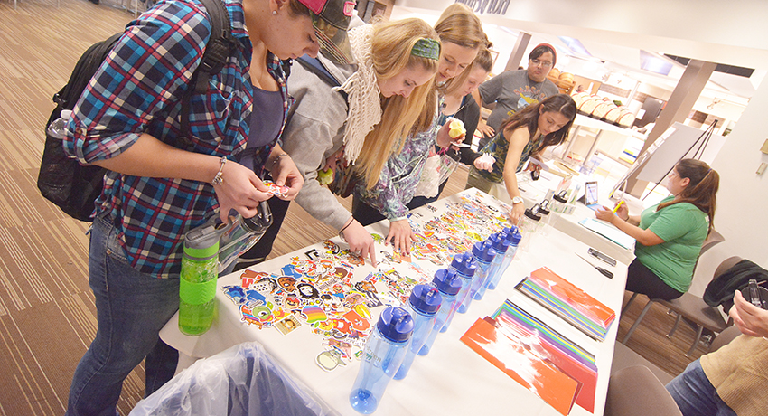 Worcester State University students decorate water bottles at Sustainability and Food Fair.