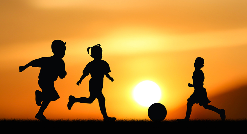 Silhouette of the children play with ball at sunset.
