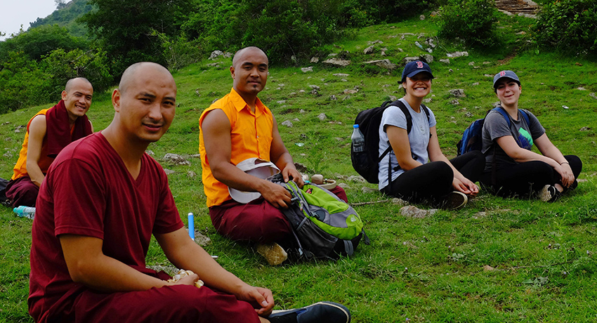 Worcester State University students sit on hillside with monks from Namdroling Monastery in India.