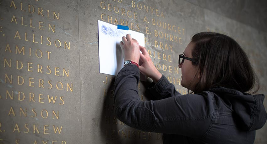 Worcester State student Nicole O'Connell does a rubbing at Memorial Auditorium.