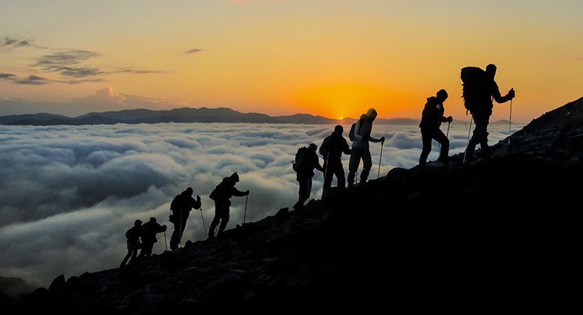 Hikers climbing the mountain above the clouds at sunset.