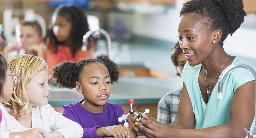 An African American teacher holding a model of a molecule